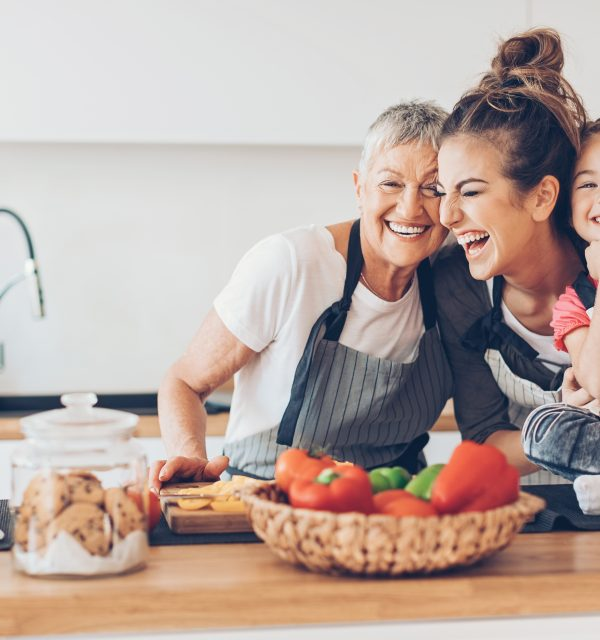 Three-generation women - grandmother, mother and small girl having fun in the kitchen, with copy space.
